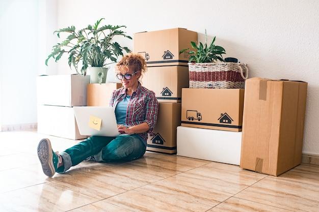 Одна молодая женщина и счастливые люди после покупки нового дома или квартиры вместе, чтобы жить вместе - человек на земле с ноутбуком с коробками и упаковками на спине