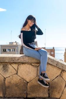 한 젊은 여자 안경 초상화, 돌로 벤치에 앉아 행복 미소, 카메라를 찾고