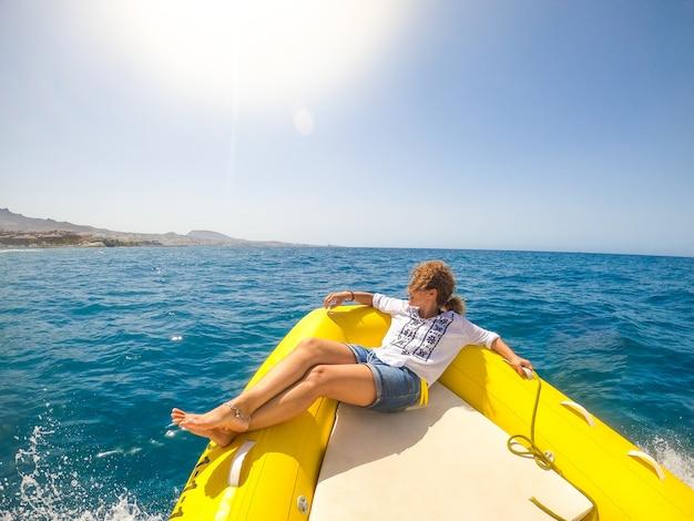 한 젊은 여성이 보트에 누워 화창한 날을 즐기고 휴식을 취하며 바다를 발견하고 작은 배에서 해안을 바라보고 있습니다.