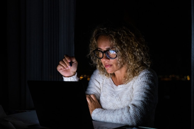 Одна молодая женщина, использующая ноутбук и работающая на компьютере ночью у себя дома. деловая женщина на работе в своем офисе