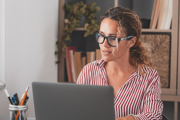 One young woman working at home in the office with laptop and notebook taking notes talking in a video conference. one businesswoman calling communicating