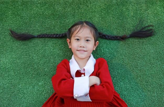 Красивая азиатская маленькая девочка в красном платье креста one рука и лежать на предпосылке зеленой травы в сезоне зимы и с новым годом.