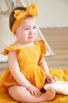 A oneyearold girl in yellow clothes is upset and crying
