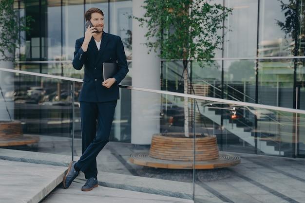 紺色のスーツを着た自信のある男性弁護士が外に立っている間笑顔でスマートフォンで話します