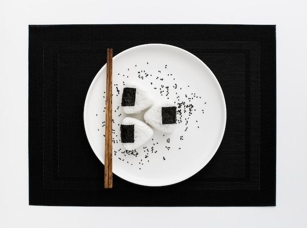 Sushi di onigri con le bacchette sulla zolla