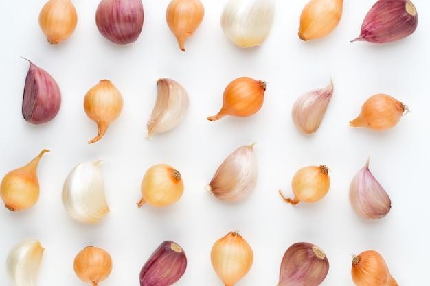Лук и чеснок, изолированные на белом фоне, вид сверху. обои абстрактный состав из овощей.