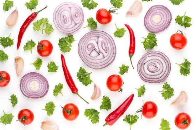 タマネギとスパイスが白い表面に分離された、上面図。野菜の壁紙の抽象的な構成。