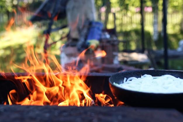 Жарить лук на огне на открытом воздухе