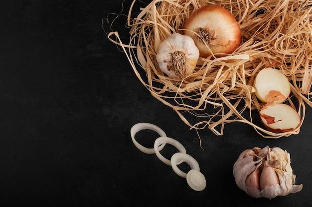 Cipolla e spicchi d'aglio sulla superficie nera.