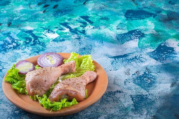 Луковые листья салата и куриная голень на глиняной тарелке