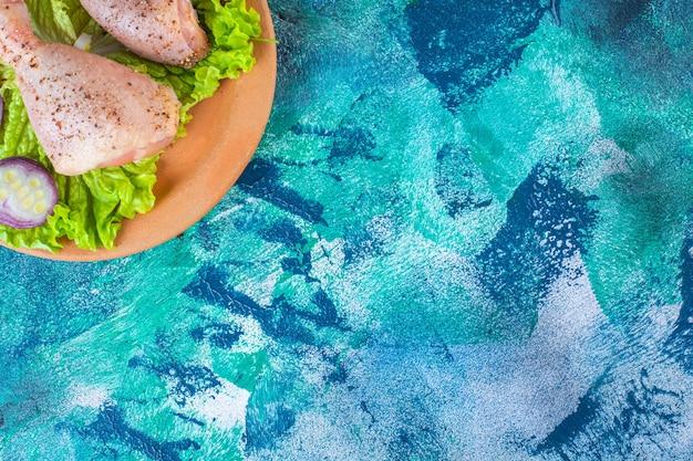 タマネギレタスの葉と粘土プレート上のチキンドラムスティック