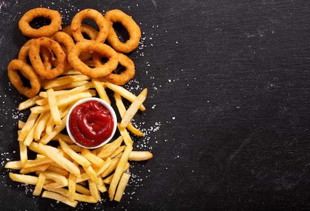 Луковые кольца и картофель-фри с кетчупом на темном столе
