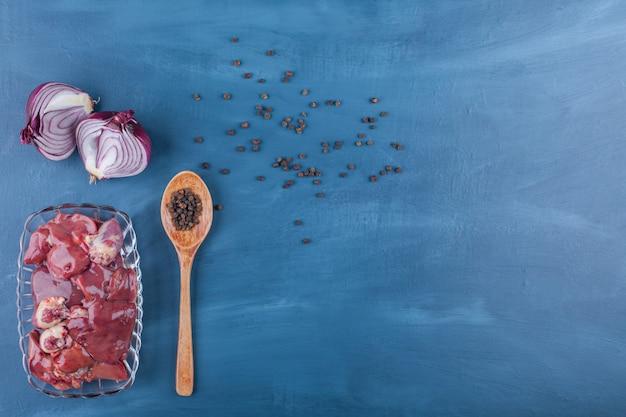 Лук, ложка, специи и субпродукты в миске, на синем фоне