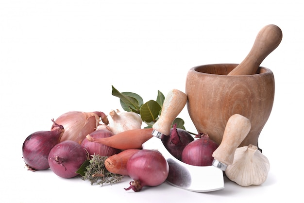 Onions, garlics and shallots with a manual chopper and pestle on white