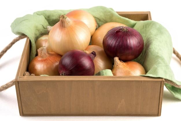分離されたリネンナプキンの美しい木製梱包箱にさまざまな品種の玉ねぎ。天然物のコンセプトです。