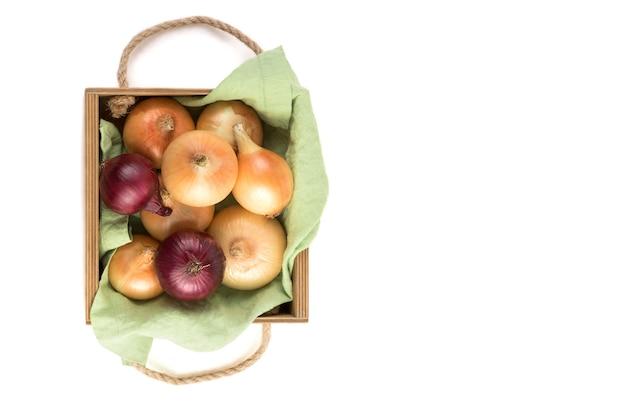リネンナプキン、分離、トップビューで美しい木製梱包箱にさまざまな品種の玉ねぎ。天然物のコンセプトです。