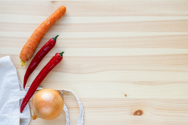 Onions, peppers and carrots on a wooden table top view