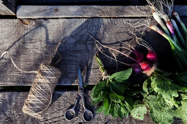 玉ねぎ、大根、ミント、古い木製のテーブル。食品の素朴な背景