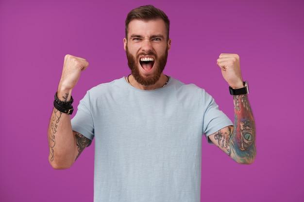 Un maschio barbuto e gioioso con un taglio di capelli alla moda con la faccia spaventata e alzando i pugni allegramente, tifando per la sua squadra preferita in viola