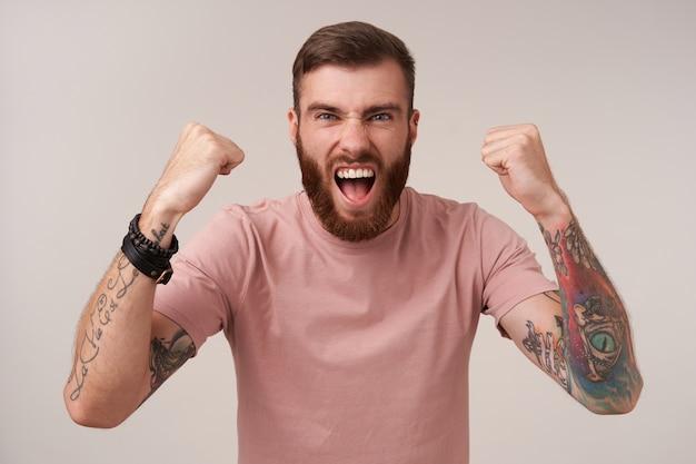 Gioioso giovane barbuto maschio tatuato con taglio di capelli alla moda che alza i pugni felicemente e urla con la bocca spalancata mentre si guarda il gioco del calcio, isolato su bianco