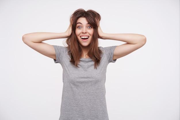 Onjoyed giovane femmina bruna stringendosi i capelli castani con le mani alzate e guardando eccitata mentre posa su bianco