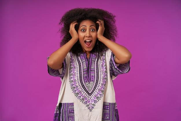 Обрадованная молодая темнокожая дама с вьющимися волосами в белой рубашке с рисунком позирует на фиолетовом с широко открытым ртом и поднимает руки к голове