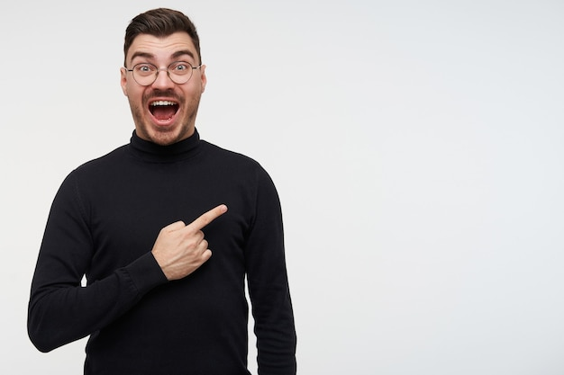 Onjoyed young handsome bearded brunette man in glasses looking excitedly with eyes and mouth opened, keeping hand raised while posing on white