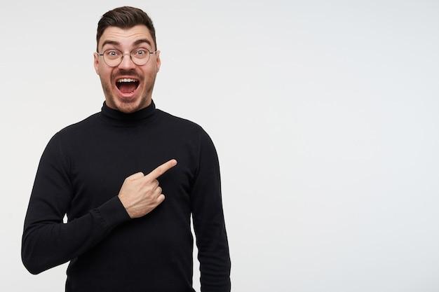 白でポーズをとっている間手を上げたまま、目と口を開いて興奮して見ている眼鏡の若いハンサムなひげを生やしたブルネットの男