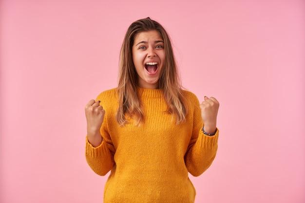 ピンクでポーズをとっている間カジュアルな服を着て、開いた広い口で幸せに叫んで、彼女の拳を上げて、自然な化粧で喜んでいる若いかなりブルネットの女性