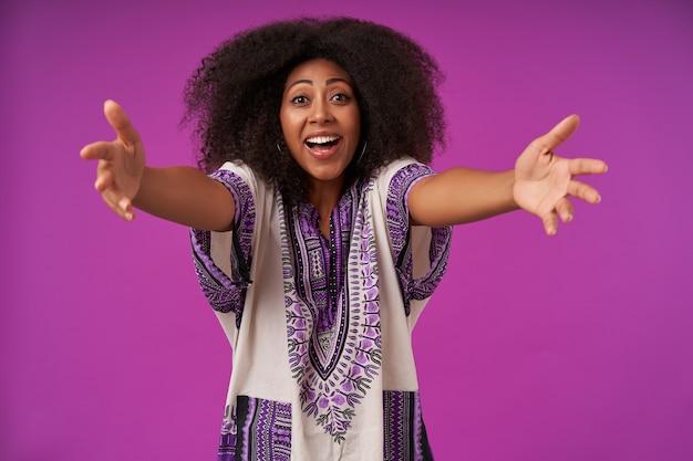 白い模様のシャツを着て、腕を広げて紫色でポーズをとり、抱擁を与えるカジュアルな髪型の若いかなり暗い肌の女性を喜ばせました