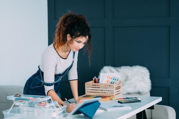 オンラインアートトレーニングスクール。タブレットでビデオチュートリアルを見て、家で絵を描くことを学ぶ女性。