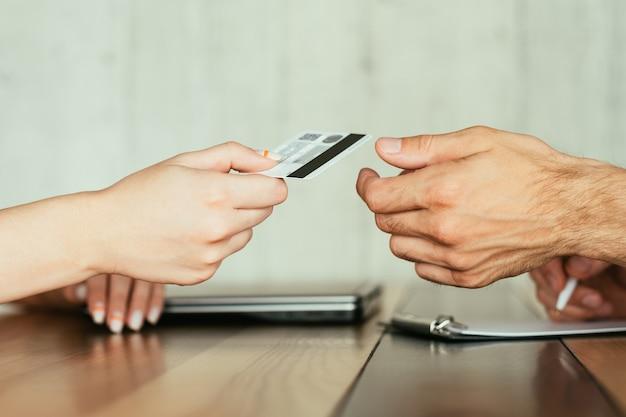 Интернет-банкинг и финансовые операции в интернете. электронные денежные переводы. два человека держат кредитную или дебетовую банковскую карту.