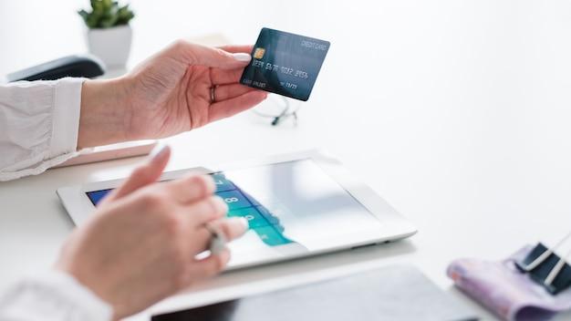 Онлайн банкинг. платеж кредитной картой. пластиковые деньги в руке. женщина, совершающая сделку. электронная оплата.