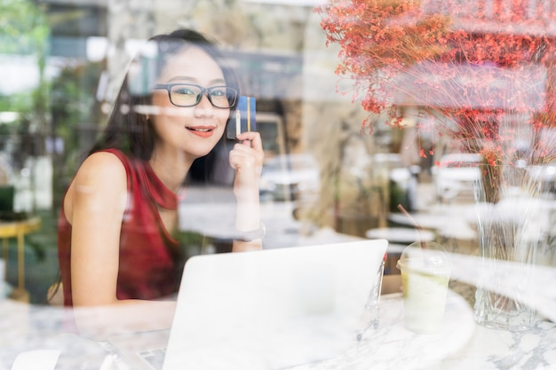 Online banking and payment concepts, young asian woman sitting smiling holding credit card in hands while shopping online on laptop in coffee shop