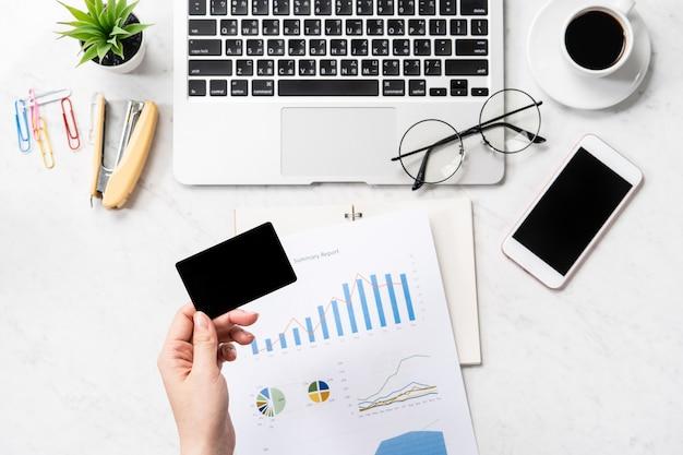 온라인 청구서 지불 개념, 대리석 배경, 복사 공간, topview, flatlay, 근접 촬영에 고립 된 사무실 책상에 신용 카드 및 모바일 휴대 전화를 모의하는 여성