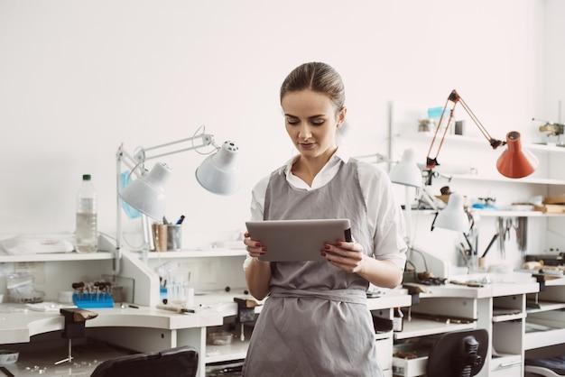 온라인 비즈니스. 그녀의 보석 작업실에 서서 디지털 태블릿을 들고 앞치마를 입은 젊은 여성 보석상의 초상화를 닫습니다. 보석 세공인. 사업. 보석 작업실. 디지털 기술