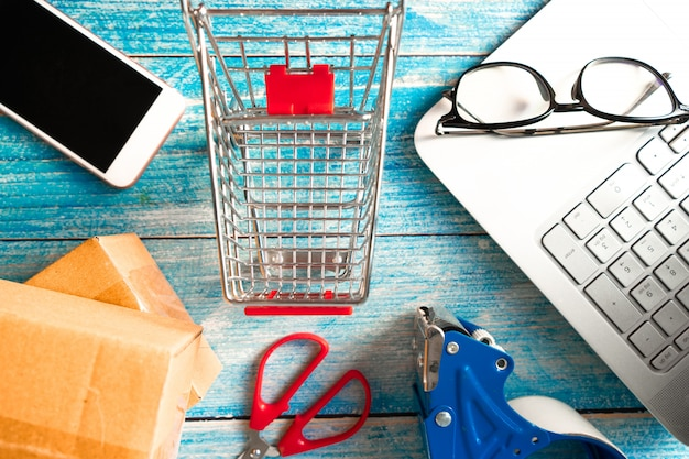 Online business concept.  shopping cart with boxes and smartphone on table