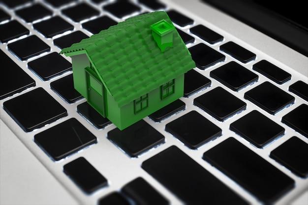 Интернет-бизнес-концепция с 3d-рендерингом зеленого дома на клавиатуре