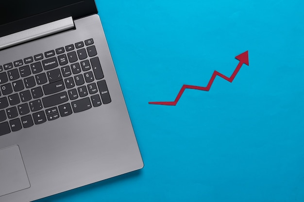 Online business, trading. laptop with red growth arrow on blue. arrow graph going up.