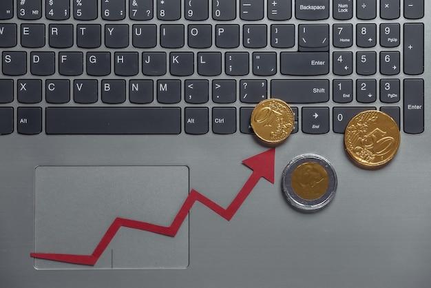 온라인 비즈니스, 거래. 노트북 키보드에 동전과 빨간 성장 화살표입니다. 올라가는 화살표 그래프.