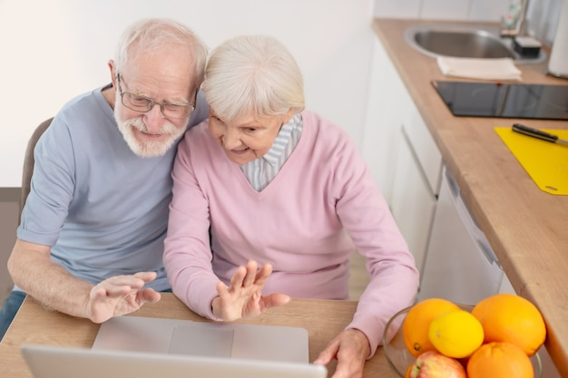 Online call. senior couple having a video call and looking happy