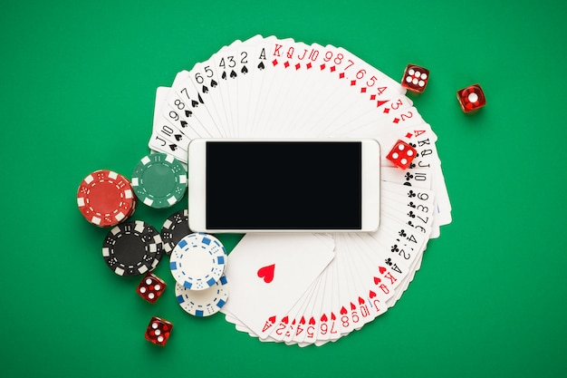Online casino concept featuring playing cards, dice chips and smartphone