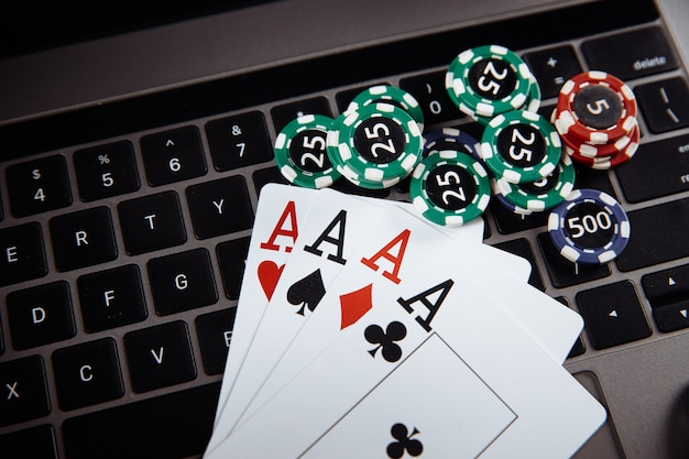 Online casino concept. gambling chips and playing cards on laptop keyboard.