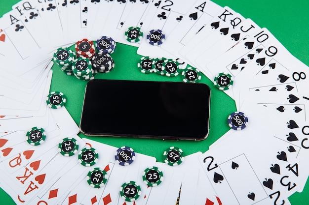 オンラインカジノのコンセプト、トランプ、サイコロチップ、グリーンテーブルにコピースペースを備えたスマートフォン。上面図。