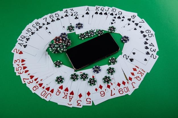 オンラインカジノのコンセプト、トランプ、サイコロチップ、グリーンテーブルにコピースペースを備えたスマートフォン。