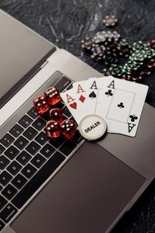 オンラインカジノ。ノートパソコンのキーボードのギャンブルチップ、エースと赤いダイスのカード。垂直方向の画像。