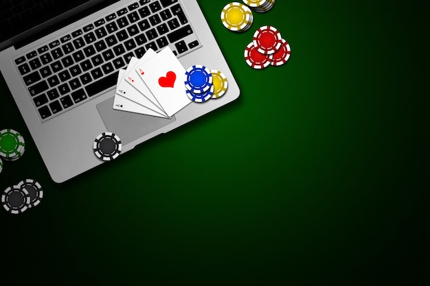 Online casino, laptop, chips cards on green