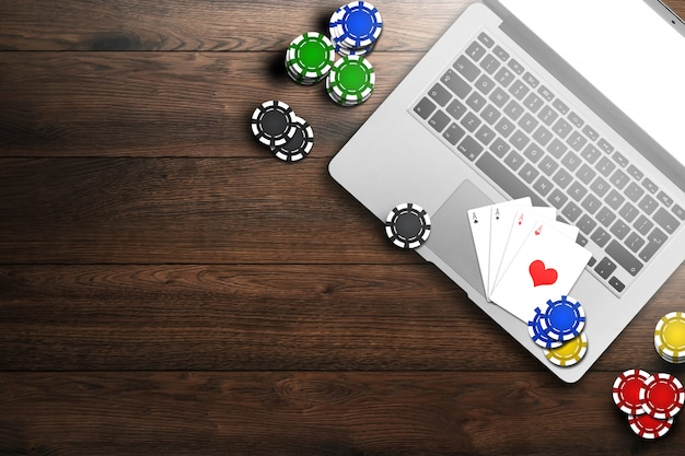 Online casino, laptop, chips cards on wood