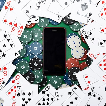 オンラインカジノ、モバイルカジノ、携帯電話、緑の背景にカードをチップします。ギャンブルゲーム。上からの眺め。