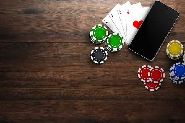Online casino, mobile casino, top view of a mobile phone, chips cards on woode